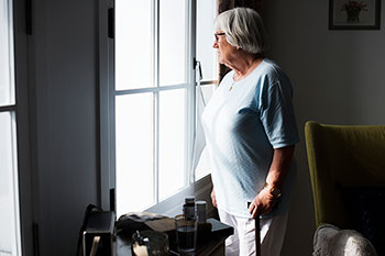 TEACH - Senior women looking out her living room window