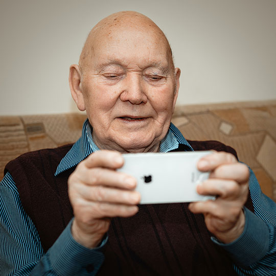 Senior man connecting iwth video chat on his iPhone